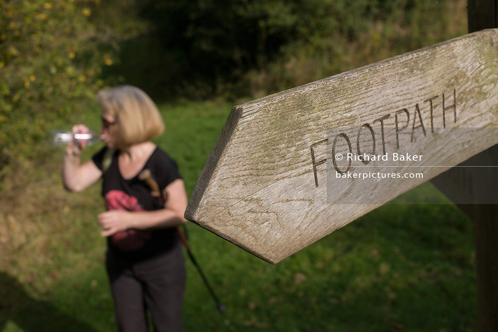 A walker drinks from a bottle next to a North Yorkshire Nationalk Park footpath sign.