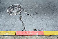 A man hole cover in a cracked concrete street near a curb painted red and yellow, Seattle, WA, USA