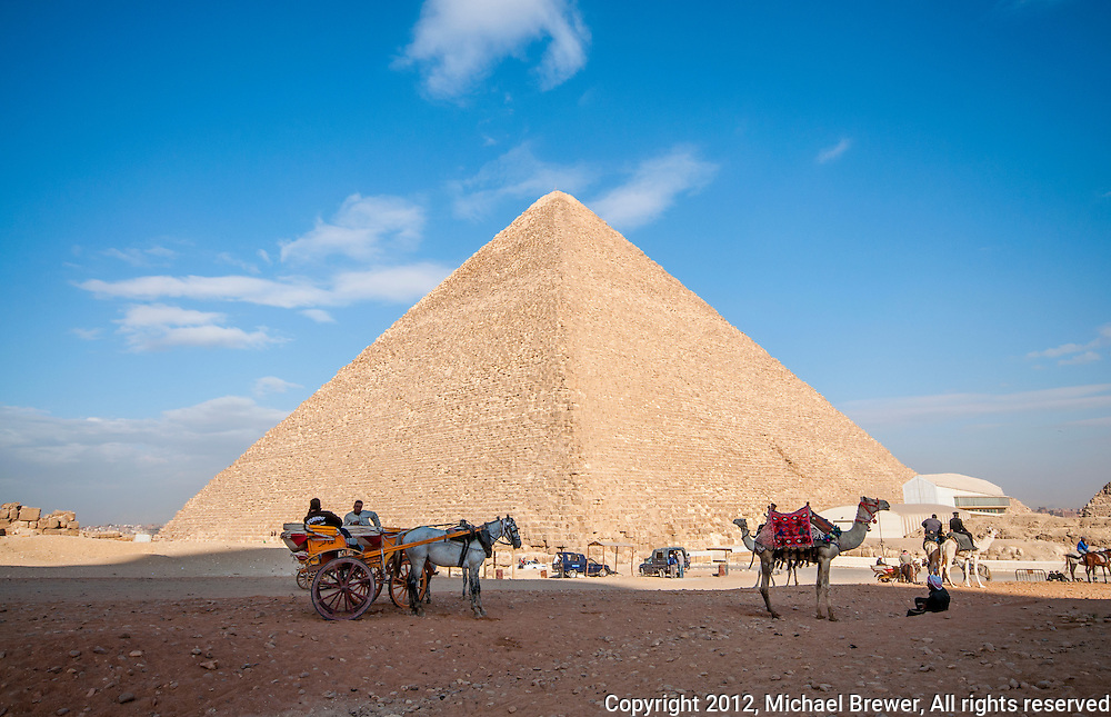 The Great Pyramid accompanied by an assortment of people, camels, horses and carts!  At Giza, Egypt.