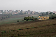 Italian farmhouse with a more modern town in the background.