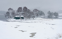 View of snow covered landscape of Loch Ossian and Loch Ossian Youth Hostel in Highland Region, Scotland, UK