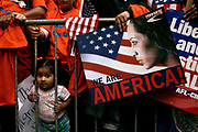 Manhattan, New York, USA, 20060410: Jennifer Bermeo, 18 months, peeks out from behind the bars of the barricades, following the rally with her family - all living in New York. Hundreds of thousands of immigrants and their supporters marched in U.S. cities on April 10, 2006 waving American flags and demanding their rights. Photo: Orjan F. Ellingvag/ Corbis