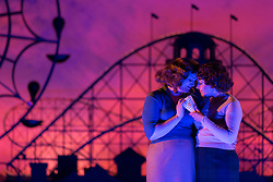 "© Licensed to London News Pictures. 14/05/2014. London, England. Kate Valentine as Fiordiligi and Christine Rice as Dorabella. Dress rehearsal of the Wolfgang Amadeus Mozart opera ""Così fan tutte"" at the London Coliseum. A new ENO production of Mozart's dark comedy set in the world of a 1950's Coney Island funfair. With Kate Valentine as Fiordiligi, Christine Rice as Dorabella, Marcus Farnsworth as Guglielmo, Randall Bills as Ferrando, Mary Bevan as Despina and Roderick Williams as Don Alfonso. Directed by Phelim McDermott, Conductor: Ryan Wigglesworth. Co-produced by the English National Opera and the Metropolitan Opera, New York. In collaboration with Improbable. 12 performances from 16 May to 6 July 2014. Photo credit: Bettina Strenske/LNP"