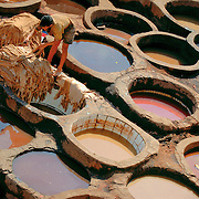 Man working in the dying pits of the tanneries in Fez, Morocco. Leather skins are dyed in the pits for weeks before being made into leather goods.