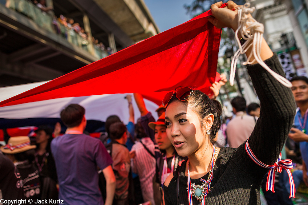22 DECEMBER 2013 - BANGKOK, THAILAND:  Anti-government protestors carry a large Thai flag down Phloen Chit Road to Ratchaprasong intersection in Bangkok. Hundreds of thousands of Thais gathered in Bangkok Sunday in a series of protests against the caretaker government of Yingluck Shinawatra. The protests are a continuation of protests that started in early November and have caused the dissolution of the Pheu Thai led government of Yingluck Shinawatra. Protestors congregated at home of Yingluck and launched a series of motorcades that effectively gridlocked the city. Yingluck was not home when protestors picketed her home.    PHOTO BY JACK KURTZ