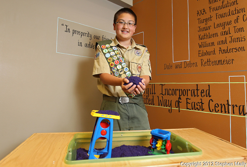 Kenny Plume, 14, of Cedar Rapids, holds fun sand in his hands next to the sensory tables he built for his Eagle Scout project at the Arc of East Central Iowa, 680 2nd St SE #200, in Cedar Rapids on Wednesday afternoon, May 16, 2012. (Stephen Mally/Freelance)