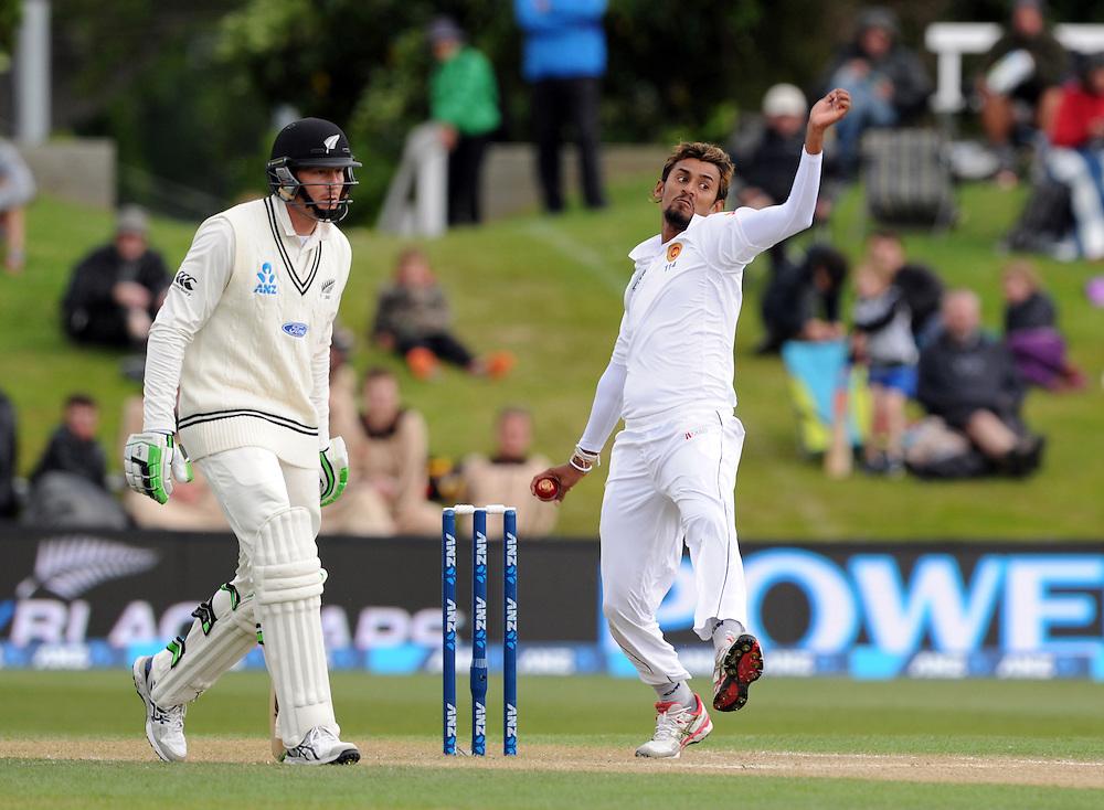 Sri Lanka's Suranga Lakmal, right, bowls past New Zealand's Martin Guptill on day three of the first International Cricket Test, University Cricket Oval, Dunedin, New Zealand, Saturday, December 12, 2015. Credit:SNPA / Ross Setford