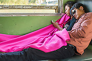 07 JANUARY 2013 - KANCHANABURI, THAILAND:   A couple sleeps in a third class train car on the train between Bangkok (Thonburi station) and Kanchanaburi. Thailand has a very advanced rail system and trains reach all parts of the country.    PHOTO BY JACK KURTZ