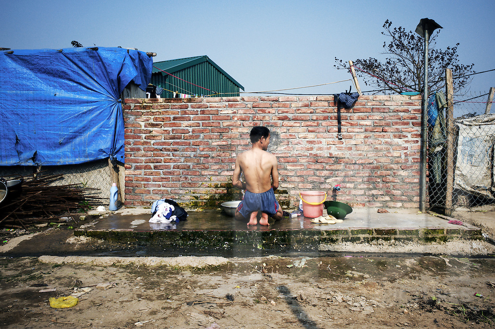 Worker bathing outdoor at a construction site in Hanoi, Vietnam