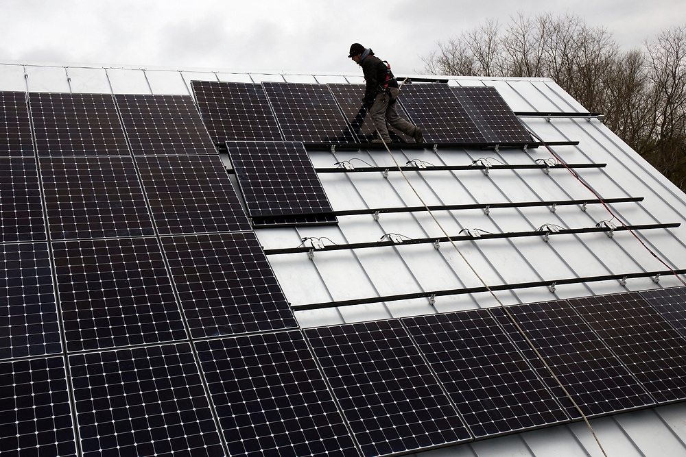 Peck Electric subcontractor Aaron Cosner works to install 60 SunCommon 320-watt solar panels on the Southern-facing 150-year-old barn at 4 Corners Farm in Newbury, Vt., on May 9, 2017. A new roof and structural work was done before the solar system was put in place. (Photo by Geoff Hansen)