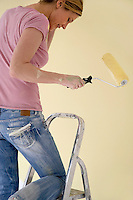 Woman on ladder with paint roller