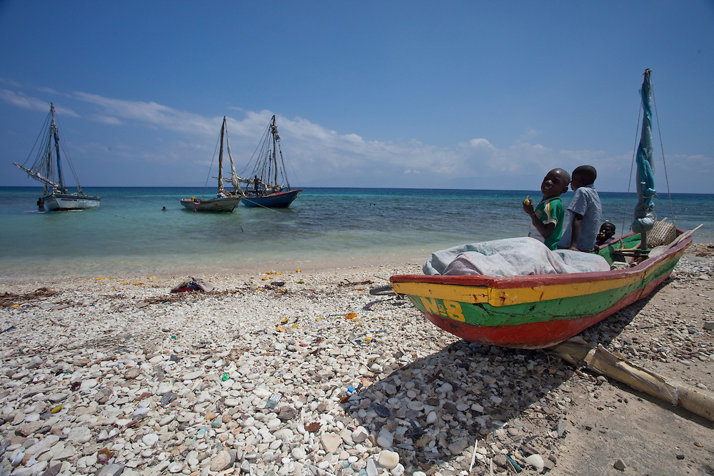 Children rest on a boat on the beach at Anse a Galet, Ile de la Gonave, Haiti