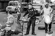 Oakland officials clean the sidewalk after temporarily removing the people who are homeless there at Northgate Avenue and Sycamore Street on Thursday, May 25, 2017, in Oakland, Calif.
