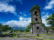 21 JANUARY 2018 - DARAGA, ALBAY, PHILIPPINES: The belltower is all that remains of the Casagawa Catholic church. The rest of the church was destroyed in the 1814 eruption of the Mayon volcano, which is in the background. Mayon volcano, the most active volcano in the Philippines.  More than 30,000 people have been evacuated from communities on the near the Mayon volcano in Albay province in the Philippines. Most of the evacuees are staying at schools in communities outside of the evacuation zone.    PHOTO BY JACK KURTZ