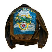 "This type A-2 flight jacket belonged to Calvin E. McCart, a tail gunner attached to the 570th squadron of the 390th Bomb Group. On the front left of the jacket is the 570th squadron insignia patch, a joker with 4 aces behind it. The name ""Mac"" is painted on the front right of the jacket, a man parachuting is painted below the name. McCart flew 35 successful missions over Europe, this is signified by the 35 bombs painted on the sleeves of his jacket. The name ""Shuttle-Babe"" is painted on the back of the jacket above artwork. The artwork on the back of the jacket is a B-17 flying through the clouds with the 8th Air Force logo behind the plane. Throughout the course of his 35 missions McCart survived 3 emergency landings."