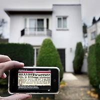 Nederland,Bilthoven , 21 november 2012..De app Hier was het nieuws geeft antwoord op de vraag: Wat is hier ooit gebeurd? De app toont - overal in Nederland - historische krantenartikelen over de locatie waar jij je bevindt. Wil je weten wat er vroeger bij jou in de buurt gebeurde? Download dan de app voor het nieuws van toen. Laat je verrassen door historische gebeurtenissen in kranten van vroeger.?Op de foto:  Het verhaal van de villa die in 1939 afgebrande villa te lezen op de Iphone of I-Pad via de App van de Koninklijke Bibliotheek..Op de achtergrond de plek op Koppellaan 3 waar nu een recenter huis staat..Foto:Jean-Pierre Jans