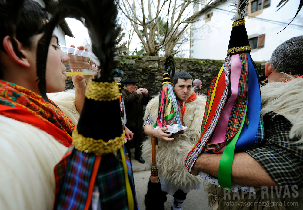 """A group of """"Joaldunak"""" (""""those who play the bell"""")drink some cider after marching carrying big cowbells tied to their backs as they take part in the ancient carnival of Ituren, in the northern Spanish province of Navarra province, on January 30, 2012."""