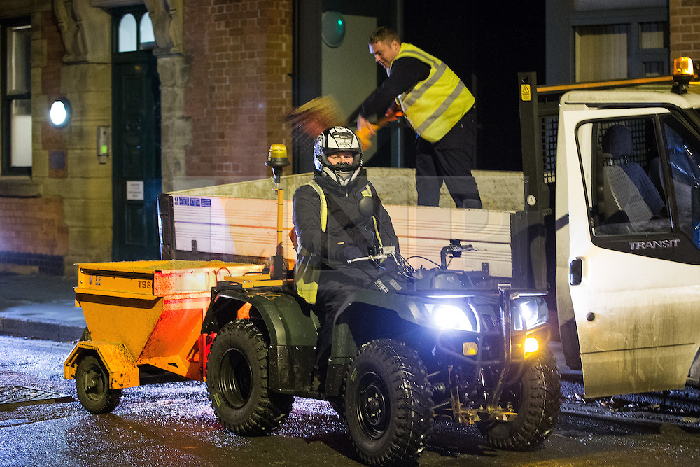 © Licensed to London News Pictures . 05/12/2014 . Manchester , UK . Staff from Mancehster City Council fill the gritter's hopper . As temperatures fall below freezing and snow is forecast , a modified quad bike with a grit hopper towed behind is driven along pavements in Manchester City Centre , gritting the walkways in its path . The specialised vehicle shares the pavement with commuters heading home at the end of the week and revellers heading for a night out . Photo credit : Joel Goodman/LNP