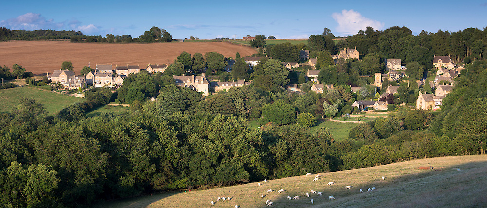 Sheep grazing by quaint traditional village of Snowshill in The Cotswolds, Gloucestershire, UK