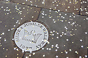 A floor sign for the Silver Jubilee Walkway 1977 opposite the House of Commons. The pavement has been sprinkled in gold an silver confetti stars.