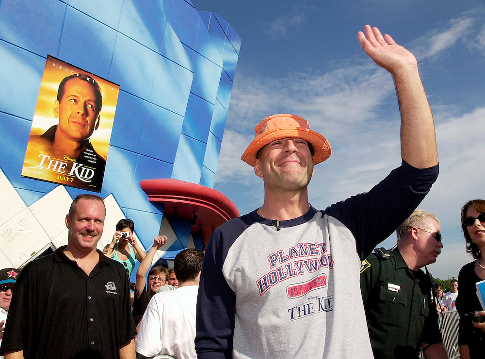 """Bruce Willis waves to the crowd as travels the red carpet on Thursday, July 13, 2000 at Planet Hollywood located in Downtown Disney is Lake Buena Vista, Fla. Willis was on hand to welcome NBA superstar Shaquille O'Neal into the Planet Hollywood family. O'Neal recently became a shareholder in the company. Willis is currently starring in Disney's """"The Kid"""" which is in theatres now.(Corbis-Sygma Photo/Scott Audette)"""