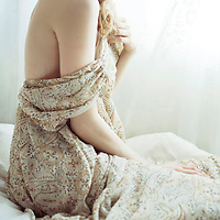 Portrait of young woman sitting on bed in front of window wearing a light summery dress with open back