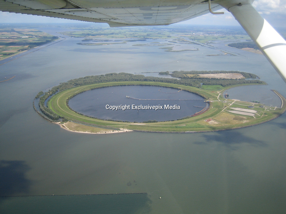 """IJsseloog: A Sludge Storage Tank in the Middle of a Lake<br /> <br /> IJsseloog, or the """"Eye of IJssel"""", is an enormous circular pit in the middle of Ketelmeer lake in the mouth of the river IJssel, in the province of Flevoland, the Netherlands. The pit is one kilometer across and 45 meters deep and functions as a storage tank for heavily contaminated slit that is still being dredged from the bottom of the lake.<br /> Between 1950 and 1990, lake Ketelmeer became heavily polluted from toxic industrial run-offs carried by Rhine and IJssel river from industries and factories located upstream. These pollutants were released into the river by industries not only in Holland but in Germany, Switzerland and France as well. The polluted sediments settled to the bottom of Ketelmeer in a thick layer of contaminated sludge. It was feared that the pollutants could contaminate the ground water or spread to the connected fresh water lake of IJsselmeer, which is the largest lake in the Netherlands and a major source of fresh water for both agriculture and drinking. The IJsselmeer also offers a number of opportunities for recreational activities such as yacht sailing.<br /> In the 1994 a decision was made to remove the polluted sediments from the lakebed. Removing the slit will also deepen the channel leading to the mouth of the IJssel, thus improving access to the river for navigation. There was, however, the problem of disposal. The slit couldn't be disposed on land without being a nuisance to agriculture and for local residents, and it also posed a serious health hazard due to presence of toxic substances and metals such as cadmium, nickel, lead, arsenic, and mercury. Therefore it was decided to store the contaminated sludge in an enormous pit called IJsseloog, situated on the lake itself.<br /> IJsseloog was constructed between 1996 and 1999. It has a diameter of 1 kilometer and depth of 45 meters and a capacity to hold 20 million cubic meters of sludge. The pit is surrounded by"""