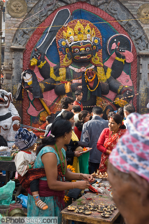 "This 12 foot high stone image of Kala Bhairava, a diety important to the Newars, was sculpted in the 17th century, in Durbar Square (or Hanuman Dhoka), in Kathmandu, Nepal. Shiva appears as Bhairab in his terrifying mode. Bhairab can appear in 64 different ways, none of them pretty. ""Telling a lie while standing before Kala Bhairab will bring instant death."" Kala means black, and Bhairava is Sanskrit for ""Terrible"" or ""Frightful"" (also known as Kala Bhairab, Bhairava, Bhairo, Bhairon or Bhairadya). Published in Silkroad inflight magazine for Dragonair September 2013 issue by Bauer Media Hong Kong."