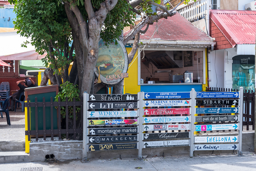 Gustavia, St Barths-- April 25, 2018. Street signs in front of a snack bar in Gustavia, St. Barth's advertise stores. Editorial Use Only.