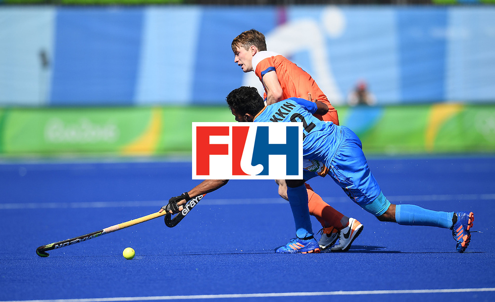 India's Chandanda Thimmaiah stretches for the ball with Netherland's Seve van Ass during the men's field hockey Netherland's vs India match of the Rio 2016 Olympics Games at the Olympic Hockey Centre in Rio de Janeiro on August, 11 2016. / AFP / MANAN VATSYAYANA        (Photo credit should read MANAN VATSYAYANA/AFP/Getty Images)
