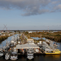 Fishing vessels are docked inside Empire Marina an protected by the Empire Floodgate a $65.8 million structure built by the Army Corps of Engineers to protect the area from storm surge in Empire, Louisiana, U.S., on Tuesday, December 19, 2017. Louisiana is preparing recommendations through projects with LA Safe for emptying out coastal areas that are unprotected by levees and will be impacted by sea level rise in the coming years. Photographer: Derick E. Hingle/Bloomberg