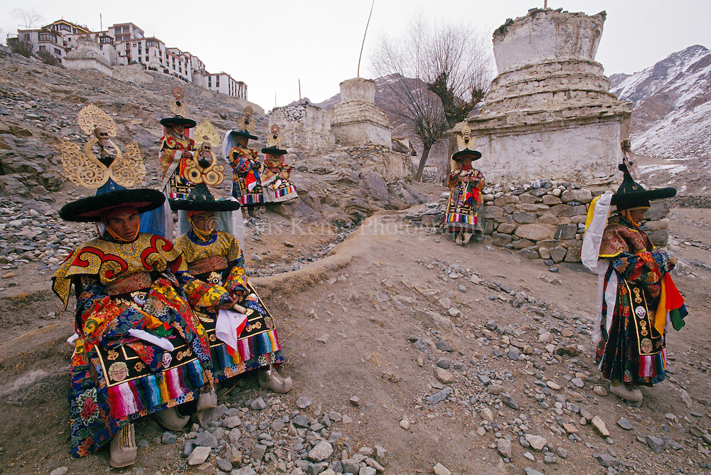 Monks in traditional costume used during festivals for performing religious dances, take a break outside the pagoda. Ladakh, India, 2002