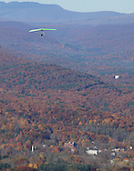 Ellenville, NY - A hang glider soars above autumn trees with the Catskill Mountains in the background on Oct. 25, 2009.