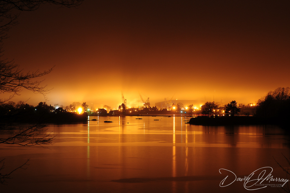 Portsmouth Naval Shipyard viewed from New Castle at night through fog, in eerie glow of sodium lights