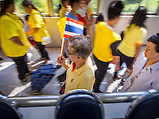 28 NOVEMBER 2014 - BANGKOK, THAILAND:  People in yellow and carrying Thai flags walk through the lobby of Siriraj Hospital, home of Bhumibol Adulyadej, the King of Thailand before the King's birthday. The King was born on December 5, 1927, in Cambridge, Massachusetts. The family was in the United States because his father, Prince Mahidol, was studying Public Health at Harvard University. He has reigned since 1946 and is the world's currently reigning longest serving monarch and the longest serving monarch in Thai history. Bhumibol, who is in poor health, is revered by the Thai people. His birthday is a national holiday and is also celebrated as Father's Day. He is currently hospitalized in Siriraj Hospital, recovering from a series of health setbacks. Thousands of people come to the hospital every day to sign get well cards for the King. People wear yellow at events associated with the King because he was born on a Monday, and yellow is Monday's color in Thai culture. It's also the color of the monarchy.      PHOTO BY JACK KURTZ
