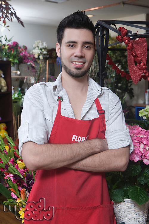 Florist stands with arms folded