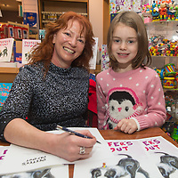 Muireann McMahon getting a signed copy of Deefers Day Out by author Etain McCooey's at Ennis Book Shop