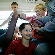 "-Trumpet player David Vande Zandschulp gets a freshman hazing as other band members create an ""Alfalfa"" look on the bus ride up to Marshall, Mn., for the first field competition of the year for the MOC Floyd Valley band.  Joe Clarey, right, pulls the hair in place while Allison Henrich stiffens it with hairspray.  Watching at left is Kyle Van Gorp.  ""I didn't mind,"" said the good-natured Vande Zandschulp.  ""I got to sit in the back of the bus with the seniors."""