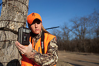 FEMALE DEER HUNTER WEARING BLAZE ORANGE DEPLOYING A GAME CAMERA