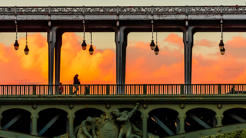A pedestrian crossing over the Bir Hakeim Bridge over the River Seine at sunset, Paris, France.