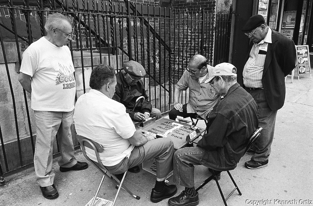 Uptown, East side, Spanish Harlem.  A group of older men sitting down to play a game of Dominos.
