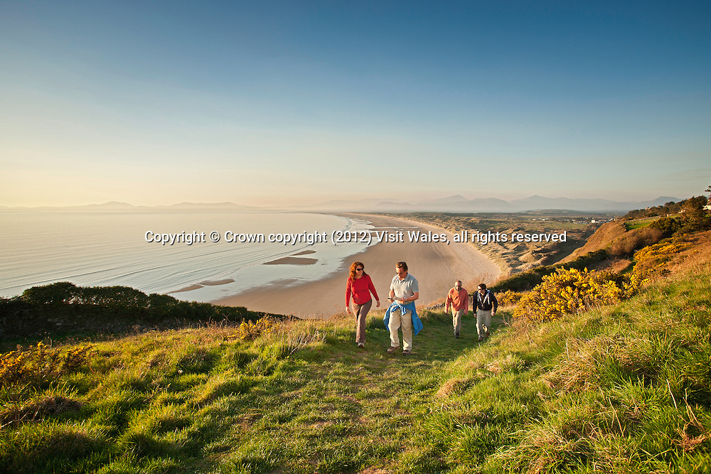 Group of friends walking and chatting in field overlooking Harlech beach<br /> Gwynedd<br /> North<br /> Walking<br /> Activities and Sports