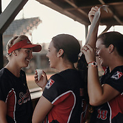Pitcher, Ellen Reed, right, helps fellow pitcher, Ivy Renfroe with her hair as teammate Amanda Fama looks on.<br /> <br /> Todd Spoth for The New York Times.