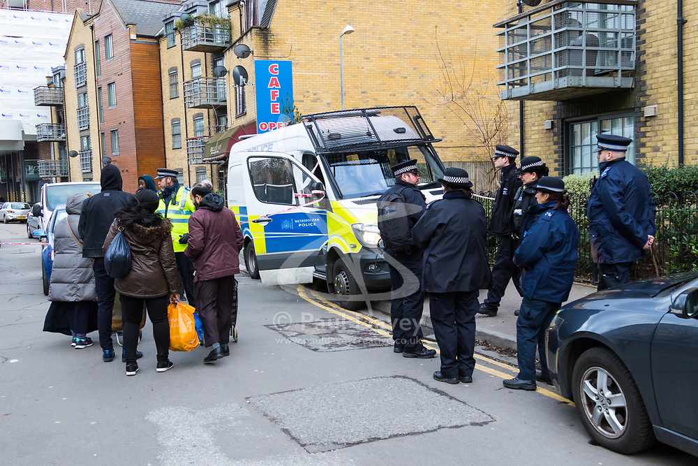 Barking, London - The scene at a housing estate on Abbey Road in Barking, London where a 19 year old died of stab wounds on 3 February 2018 despite attempts by paramedics to save his life. Scotland Yard's murder squad are investigating and have made no arrests so far. PICTURED: Local residents have to give their details to police officers manning the cordon before they can get to their properties. February 04 2018.