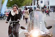 In Amsterdam haalt een jongen op een scooters een bellende fietser in op fietspad. De Fietsersbond wil samen met de gemeente Amsterdam dat bromscooters niet meer op het fietspad mogen rijden. De scooters veroorzaken veel overlast op de toch al volle fietspaden in de hoofdstad. Volgens onderzoek is het veiliger om de scooters op de hoofdrijbaan te laten rijden. Bovendien is het voor fietsers ongezond als de bromscooters met hun uitlaatgassen op het fietspad rijden. <br /> <br /> In Amsterdam scooters ride between the cyclists on the bike lane. The Dutch Cyclists Union and the municipality of Amsterdam want that moped scooters no longer allowed to ride on the bike lane.  The scooters are a nuisance to the already full bicycle lanes in the capital. According to research, it is safer to drive scooters on the main carriageway. Moreover, it is unhealthy for cyclists that moped scooters with their pollutions ride on the bike path.