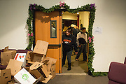A person peeks through a door to see opened boxes during a Milpitas Food Pantry event at Lifegate Church in Milpitas, California, on November 25, 2013. (Stan Olszewski/SOSKIphoto)