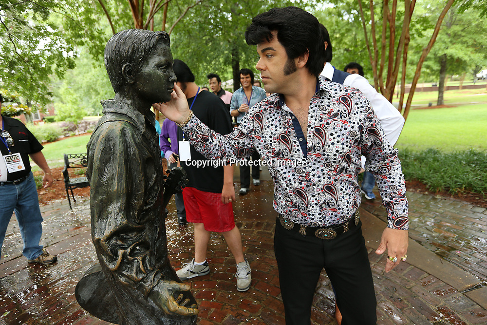 """Elvis tribute artist, David Allen, from Addison Texas, reaches out and touches the face of the """"Elvis at 13"""" statue as he and the other 18 tribute artists tour the Elvis Presley Birthplace on Friday afternoon in Tupelo."""