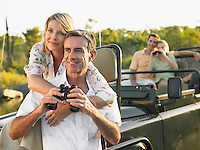 Two couples on trip one sitting in jeep using binoculars