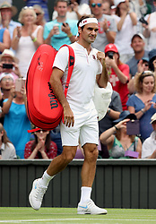 Roger Federer walks onto court on day three of the Wimbledon Championships at the All England Lawn Tennis and Croquet Club, Wimbledon.