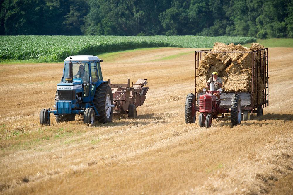 2 farmers driving tractors